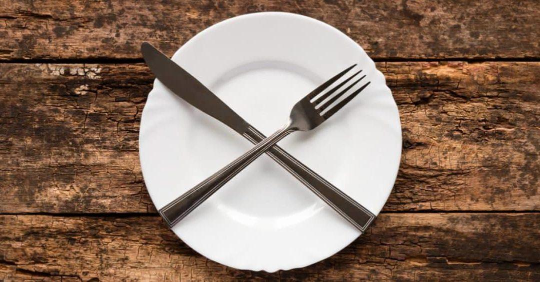 couverts croisés sur une assiette et une table en bois