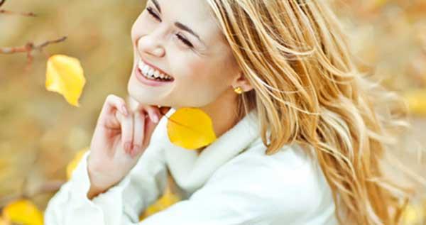 Femme blonde qui sourit et tiens une feuille d'arbre jaune