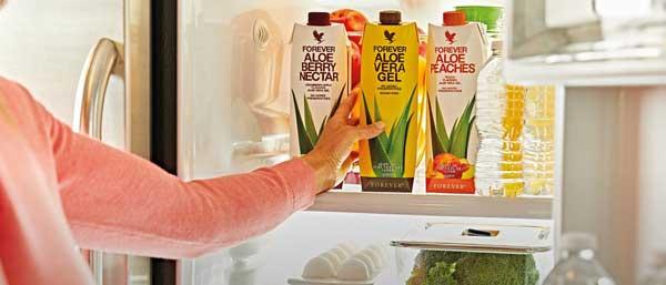 Personne qui prends une boisson aloe vera gel dans le frigo