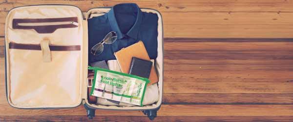 Valise ouverte avec des vetements, un porte feuille et des lunettes