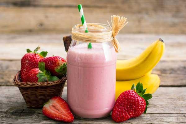 smoothie fruit avec une paille et de vrais fruits autour sur une table en bois